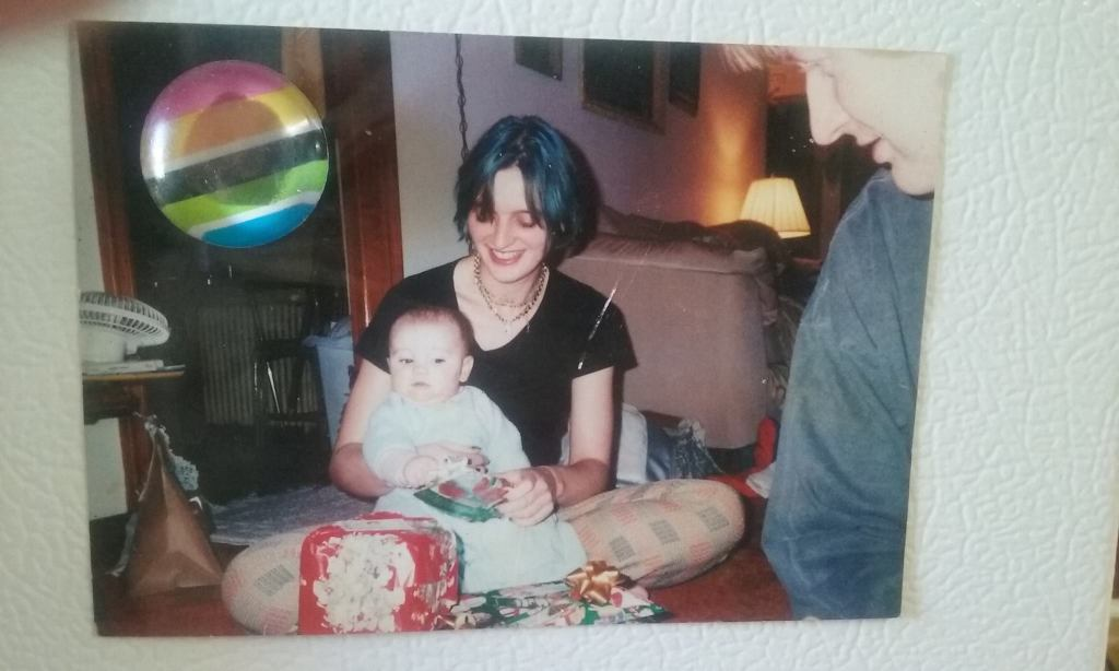 Old photograph on a refrigerator of a blue-haired young woman with a baby on her lap at Christmas