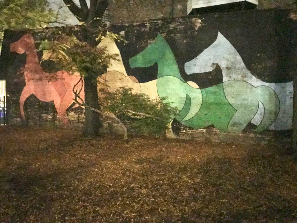 Five horses in red, orange, yellow, green, and blue painted on a black background on a brick wall with a tree blocking most of the orange horse